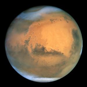 Hubble-teleskoopin ottama kuva Marsista, jossa on kehittymässä myrsky sekä pohjoisnavalla että oikeassa alakulmassa ns. Hellas-tasangolla. Kuva: ESA Hubble.