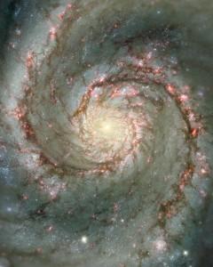 """Tässä on M51 eli """"pyörremyrsky"""". Näkyvän valon muodostamaa kuvaa on täydennetty erikoiskameran ottamalla kuvalla punaisista vetypilvistä, jotka hehkuvat uusien tähtien ympärillä. Kuva: ESA Hubble."""