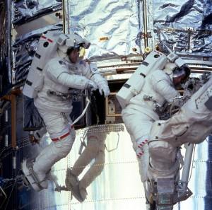 Astronautit C. Michael Foale (vas) ja Claude Nicollier huoltavat Hubble-teleskooppia. Kuva: ESA Hubble.